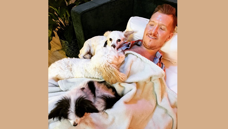 Kevin snuggling with his dogs