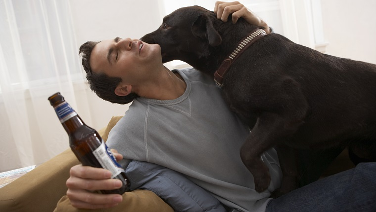 Man holding bottle with dog licking his face