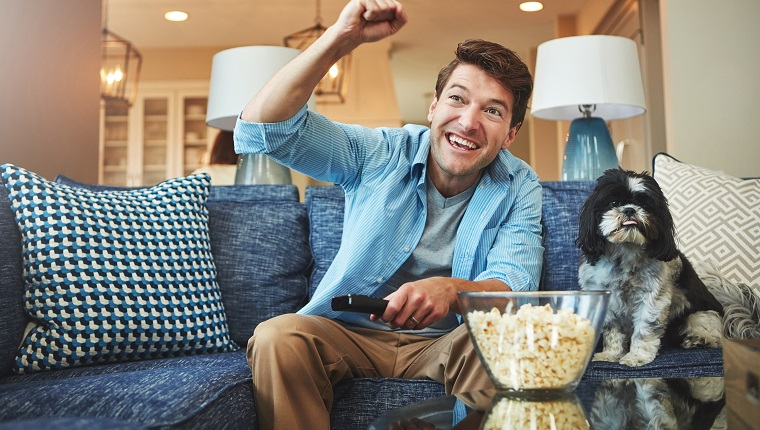 Shot of a happy man celebrating while watching a sports match on tv