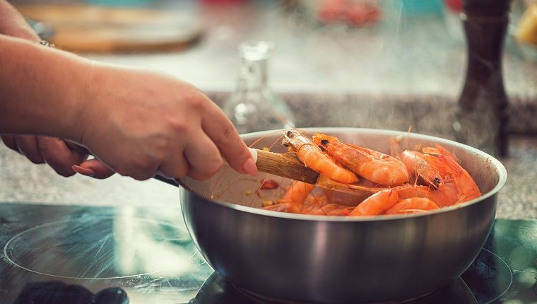 Young women preparing shrimps with white wine,chili pepper and parsley at home