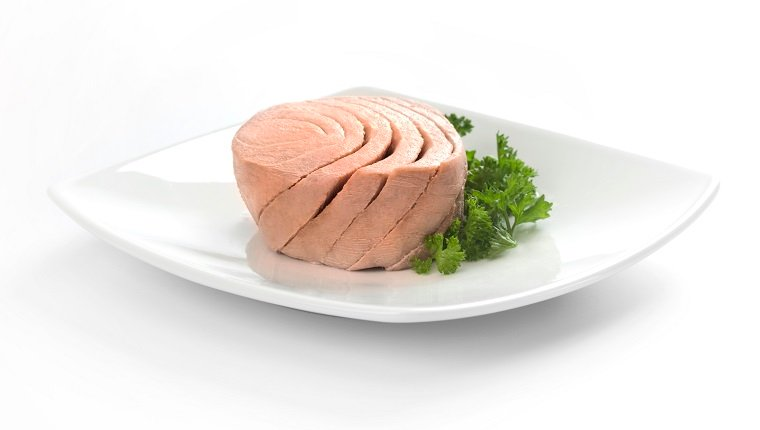 Canned tuna portion served on white dish with parsley.